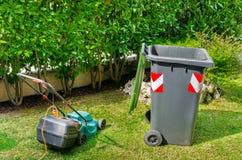 回收站和一名电搬家工人在草坪 免版税库存图片