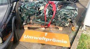 回收老,使用的,被击毁的汽车 折除在小块围场Umweltpremie德语的部分的 免版税库存照片