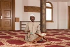 回教人在Dishdasha读古兰经 库存图片