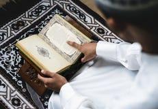 回教人坐跪毯读书古兰经 免版税库存照片