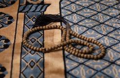 回教在地毯安置的concep-tasbih白色木小珠在清真寺回教praye伊斯兰教的信仰,概念:慈悲的文化信仰 免版税图库摄影