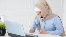 回教妇女与手机的客户谈话,做纸笔记并且看膝上型计算机屏幕 影视素材