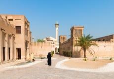 回教妇女在有清真寺的老阿拉伯区 免版税库存图片