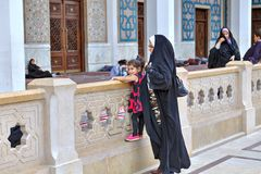 回教妇女在清真寺庭院里有小女孩的漫步 免版税库存图片