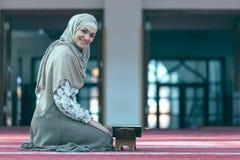年轻回教妇女读书koran在清真寺 免版税图库摄影