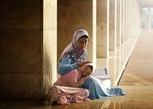 回教母亲教她的女儿读书koran 免版税库存照片