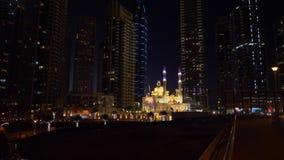 回教清真寺和现代玻璃摩天大楼与明亮的夜在迪拜市点燃 股票视频