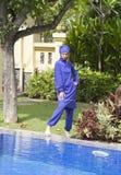 回教游泳衣burkini立场的可爱的妇女在水池边在一个热带庭院里 免版税库存图片