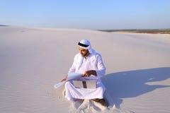 回教男性建筑师与膝上型计算机在沙子在沙漠坐h 库存照片