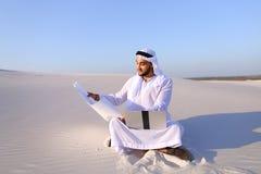 回教男性建筑师与膝上型计算机在沙子在沙漠坐h 免版税库存图片