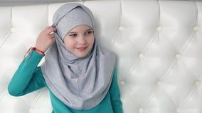 回教青少年的女孩画象灰色hijab的在照相机看 股票录像