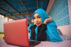 回教hijab头围巾的美丽和愉快的妇女与便携式计算机一起使用或有乐趣网络使用互联网在r 免版税库存图片
