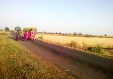 回来农村印地安草收割机的妇女在家 图库摄影