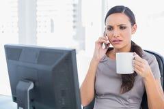 回答皱眉的女实业家拿着咖啡和电话 库存照片