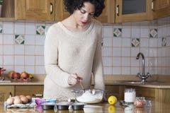 回顾一份食谱的成份的杯形蛋糕的少妇 免版税库存照片