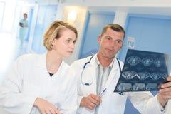 回顾在医院走廊的两位男性医生X-射线 图库摄影