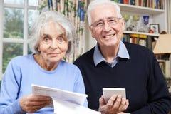 回顾在家财务的微笑的资深夫妇画象  免版税图库摄影