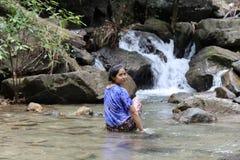 回顾在瀑布的妇女 库存照片
