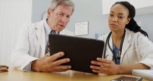 回顾患者的文件的勤勉医生 免版税库存照片