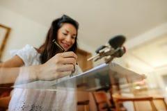 回顾物产文件的妇女在签字前 库存图片