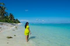 回顾年轻美丽的亚裔的女孩画象走开在海滩和 免版税库存图片