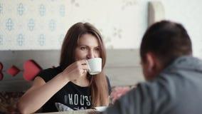 因为她有与一个人的交谈在咖啡馆,美丽的妇女食用咖啡或茶 她微笑,享受好公司 股票视频