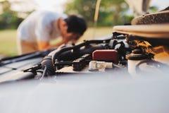 因为对路和此发生故障的他的汽车不是可能修理它,绝望的一年轻人抓住了他的头 免版税库存图片