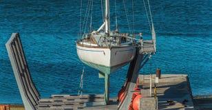 因为背景是蓝色的小船小船可能棍打浮动旅馆图象略写法海洋红色风船航行风帆被传统化的使用的通知游艇黄色的黑暗的等标志 游艇 免版税库存照片