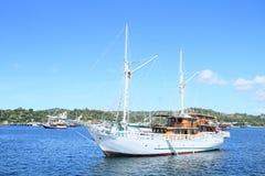 因为背景是蓝色的小船小船可能棍打浮动旅馆图象略写法海洋红色风船航行风帆被传统化的使用的通知游艇黄色的黑暗的等标志 免版税图库摄影