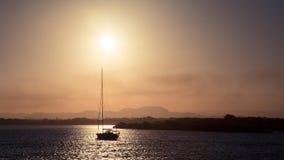 因为背景是蓝色的小船小船可能棍打浮动旅馆图象略写法海洋红色风船航行风帆被传统化的使用的通知游艇黄色的黑暗的等标志 免版税库存照片