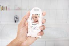 因为婴孩是醒的在婴孩显示器,做父母被赢取的` t有浴的时间 图库摄影