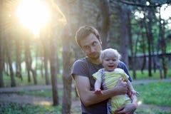 因为他的婴孩哭泣,父亲生气 免版税库存照片
