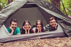 因此一起乐趣!躺下在a的帐篷的两对可爱的夫妇 库存图片