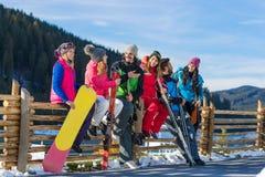因此人们编组与雪板滑雪胜地雪冬天山快乐的朋友坐木谈话 库存照片
