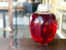 囤积居奇的红色大玻璃三升银行,汁液,与一个木盒盖的魔药在被弄脏的背景 免版税库存照片