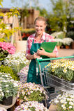 园艺中心妇女投入了盆的花推车 免版税库存照片