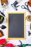 园艺工具、罐、幼木和黑板在一张白色木桌上 复制空间 顶视图 免版税库存图片