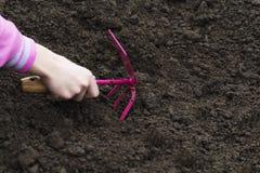园艺工具在土壤背景的手上 春天庭院运作概念 库存图片