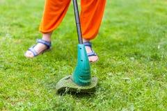 园艺设备 割与整理者的少妇草 免版税库存照片