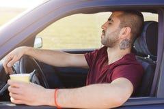 困不剃须的年轻男性在汽车坐,拿着咖啡,感到疲乏没有休息的推进汽车,停下来有断裂  库存图片