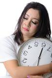 困亚洲妇女拥抱时钟 免版税库存图片