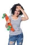 困厄的牛仔裤的愉快的女性有滑板的 免版税库存照片