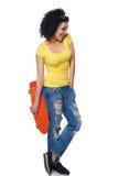 困厄的牛仔裤的愉快的女性有滑板的 免版税库存图片