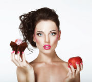 困境。饮食。有苹果计算机和杯形蛋糕的未定的妇女 库存照片
