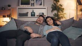 困夫妇看着电视在家后在夜打呵欠的一起说谎在长沙发 影视素材