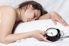 困女孩不可能从警钟醒 妇女在床上在她的手上睡觉并且拿着一个闹钟 免版税图库摄影