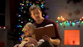 困女孩的殷勤爸爸读书圣诞节童话在装饰的树附近 库存图片
