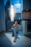 困妇女坐地板在开放冰箱在夜间 库存照片
