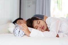 困妇女早晨关闭在一个人旁边的闹钟 库存照片