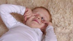 困孩子在叫醒或得到睡眠的床上 股票视频